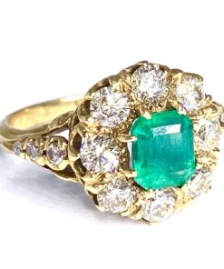 18ct yellow gold emerald and brilliant cut diamond ring. with diamond embellished shoulders.