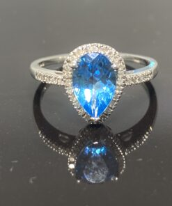 Blue Topaz Diamond Halo Ring, central pear shaped topaz surrounded with a halo of pave diamonds. The ring is in 10 ct white gold. The shoulders are set with pave diamonds also