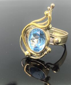 Vintage Blue Topaz Swirl Ring in hallmarked 9ct gold. This stunning, flowing ring design has a makers mark also PJC and hallmarked Birmingham 1989. The central blue topaz is faceted and has a light to mid blue topaz. The ring can be resized free