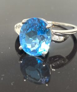 Blue Topaz & Diamond Ring in 9 ct white gold. The central mid blue faceted topaz is claw set, there are two small brilliant cut diamonds set in each side of the shoulders.