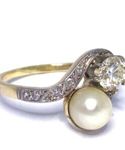 This 15ct yellow gold and platinum Edwardian ring is the definition of natural beauty. The crossover ring holds a lustrous mother of pearl and principle diamond set in platinum. The shoulders have twinkling 8 cuts in rub over setting. The shank is 15ct Gold with no Hall or Makers mark.