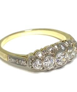 14ct Yellow Gold and Platinum five stone ring. Boat shaped top holds five principle diamonds with diamond surrounding, in rub over setting.