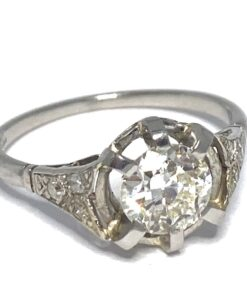 Single set, brilliant cut solitaire Diamond on a Platinum stamped shank with intricate diamond embellished grain set shoulders.