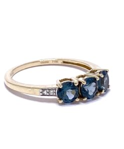 The 3-Stone London Blue Topaz Half Eternity Stacking Ring is 9ct Gold. The ring has three 4-prong set, brilliant cut, deep turquoise blue Topaz. Both shoulders are flush set with two white micro Diamonds