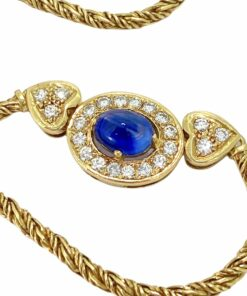 Sapphire and Diamond Heart Necklace. Cacochon Sapphire claw set amongst pavé set brilliant cut diamonds. The central oval setting is held by two hearts holding 3 brilliant cut diamonds each. The pendant sits central to a heavy double twisted rope chain with snap plate and security clasp.