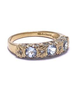 9ct Gold Three stone crystal blue Aquamarine, flush set with four star set diamonds.