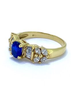 Sapphire and Diamond 18ct Gold Contemporary Ring. A claw set Sapphire surrounded by geometric baguette diamonds, and Marquise diamonds.