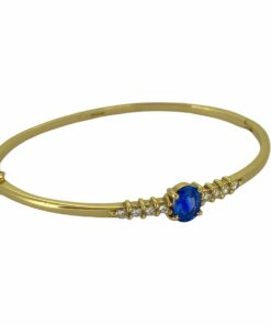 Diamond and Sapphire embellished 18ct Gold Bangle. All gemstones are claw set, the hinge is up and over with a double figure eight safety.