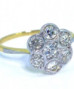 Timeless 1940's Diamond, 18ct Gold and Platinum Daisy Cluster Ring. The shank and under bezel are stamped 18ct yellow gold. Additionally, the diamonds are rub over, grain set in platinum.