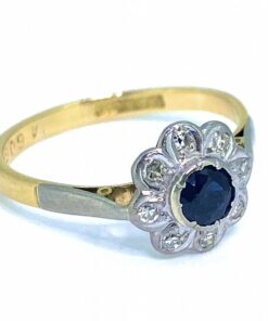 Vintage Sapphire and Diamond Daisy Cluster Ring, stamped 18ct. The cluster setting is platinum with 18ct Tiffany shank and shoulders that are topped with platinum. The faceted sapphire and diamonds are all in rub over settings.