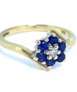 A Vintage Diamond and Sapphire Cross Over Cluster Ring, hallmarked 9ct. Six royal blue sapphires, surround the central diamond, all claw set.